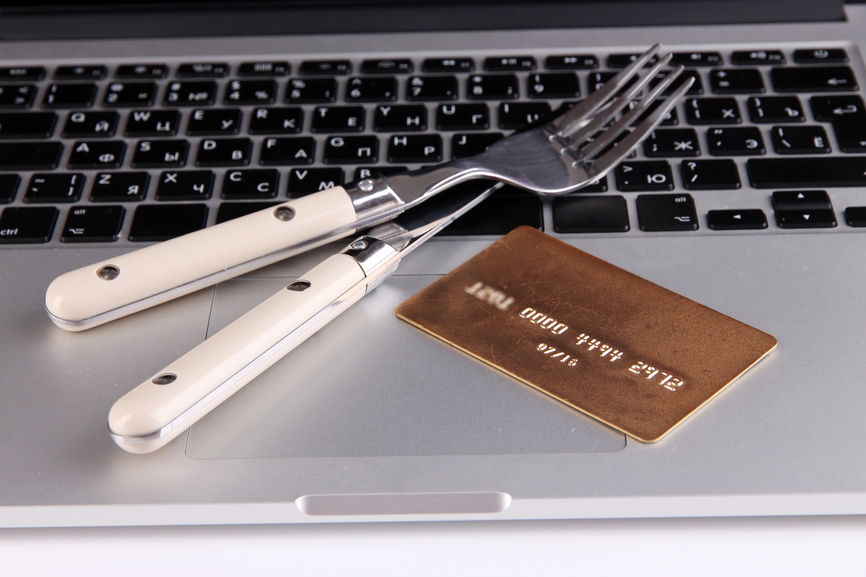 Credit card with fork and knife on computer keyboard close up