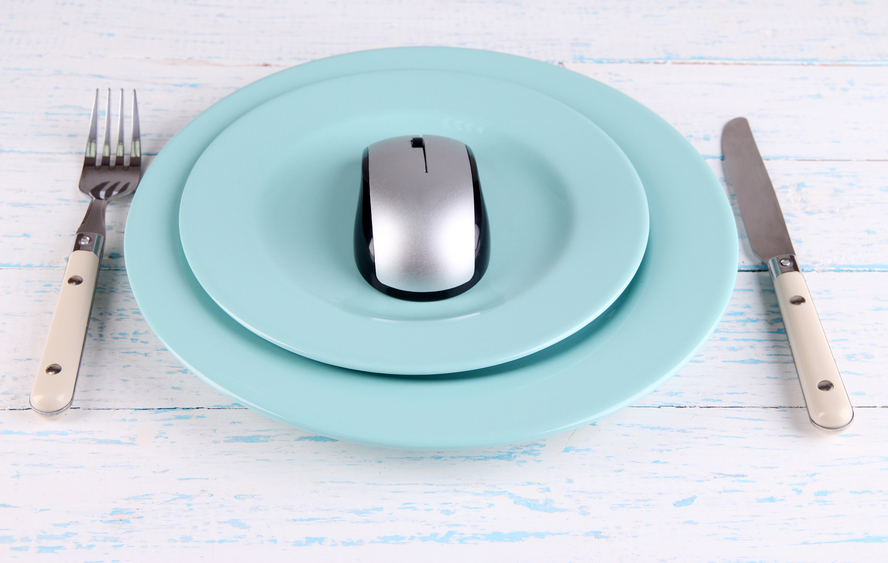 Computer mouse on plate with fork and knife on wooden background