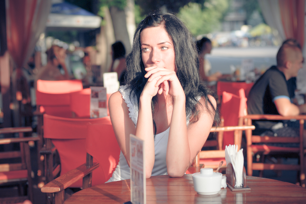 Young beautiful woman sitting at patio cafe table and waiting