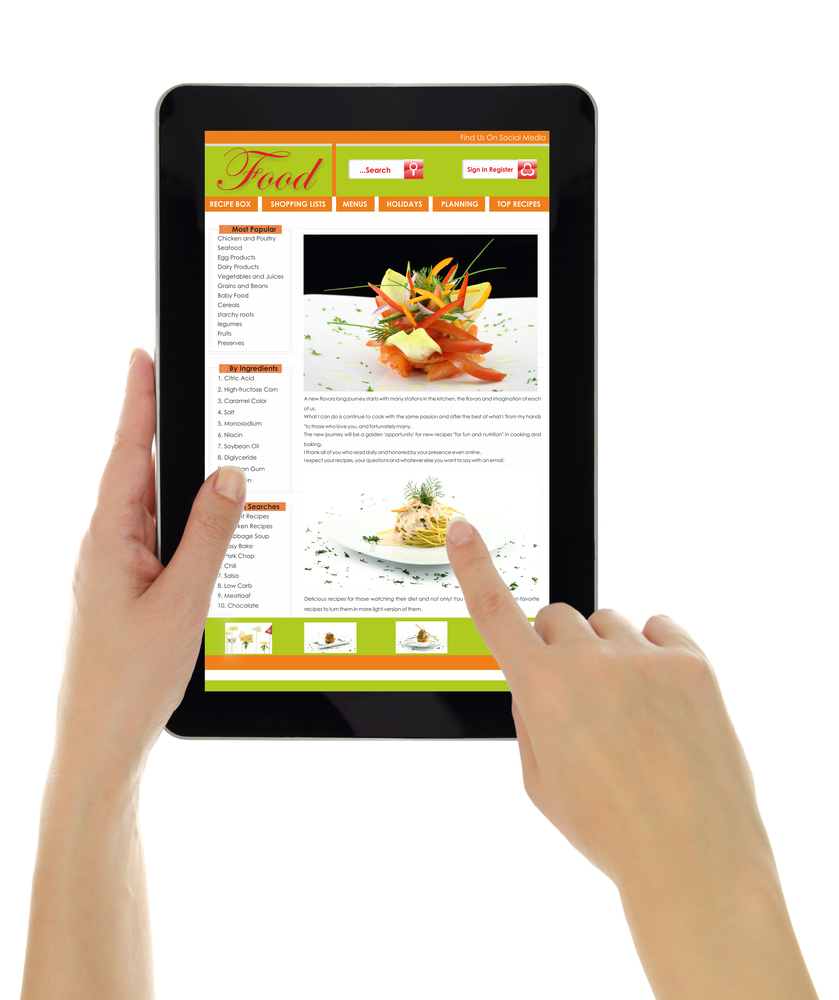 Hands holding tablet with recipe website template isolated