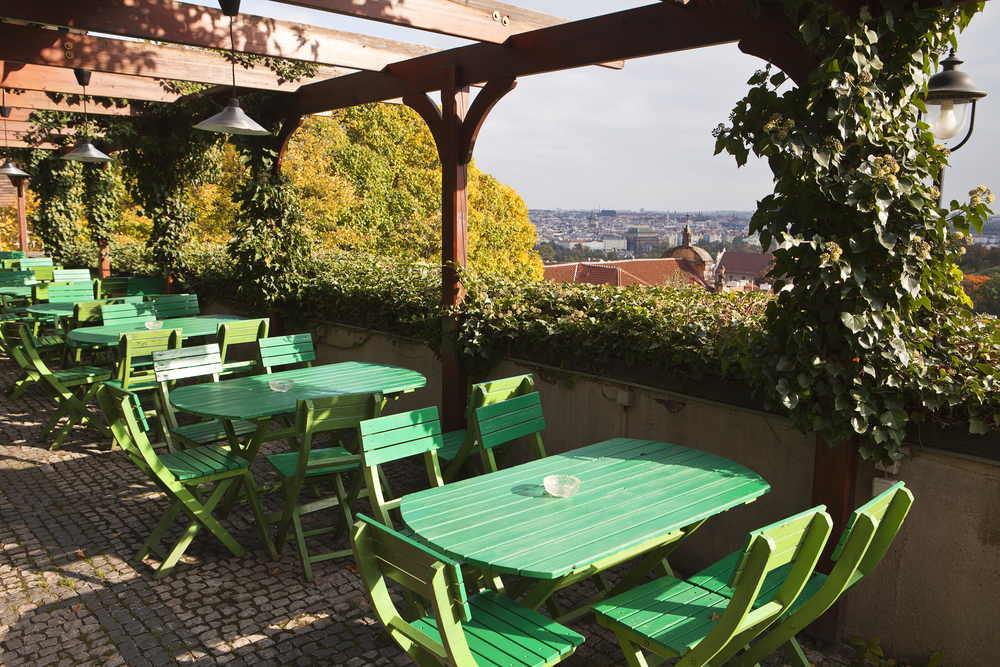 The outdoor seating area with green tables and chairs in a restaurant near the Prague Castle in the Czech Republic. In the background are the roofs of the Old Town.