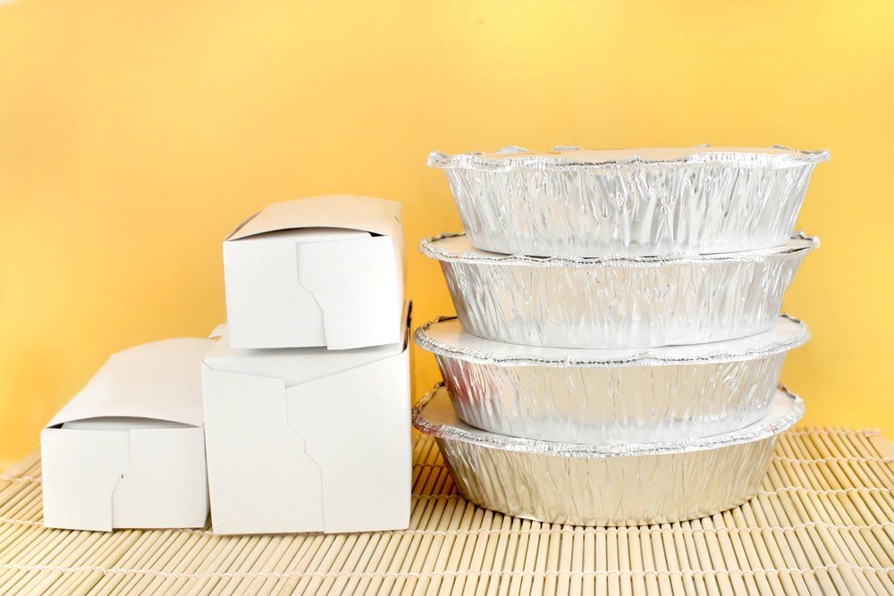chinese food delivery or takeout aluminum covered containers and cardboard boxes on bamboo placemat