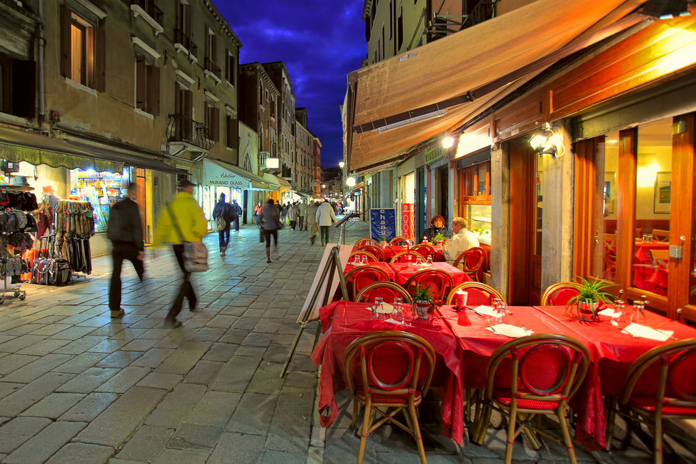 VENICE - NOVEMBER 13: Small outdoor restaurant with red tables and chairs on narrow street - is one of the many bars and restaurants popular with tourists in the evening hours on streets of Venice, Italy on November 13, 2012.