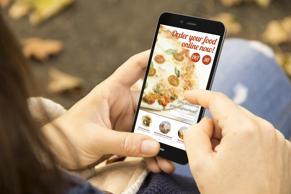 order food concept: woman holding a 3d generated smartphone ordering fast food. Graphics on screen are made up.