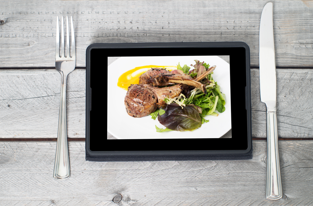 Online ordering food concept with table setting and meal course on a tablet screen
