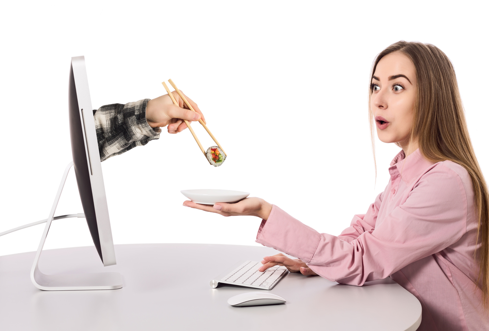 Internet Food ordering and instant Delivery young Woman makes Order at Computer Hand of Agent appears from Screen instantly giving her Order holding Sushi Roll with wooden Chopsticks white Background