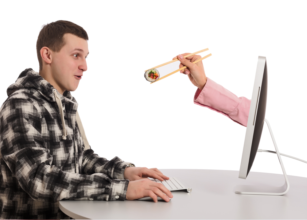 Internet Food ordering and instant Delivery young Man makes Order at Computer Hand of Agent appears from Screen instantly delivering Order holding Sushi Roll with wooden Chopsticks on white Background
