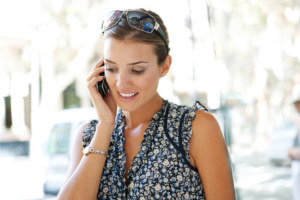 Close up portrait of an attractive businesswoman having a conversation on her smart phone in a classic city, outdoors.